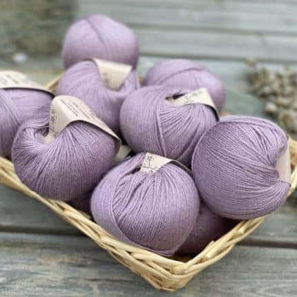 A basked of purple balls of yarn.