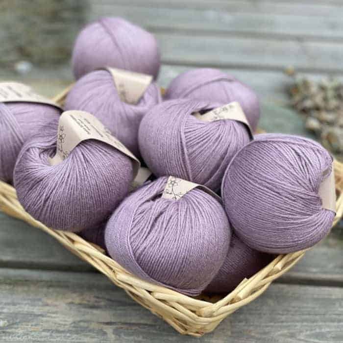 A basked of purple balls of yarn.