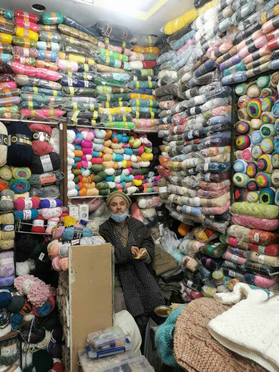 A Pakistani man sits amongst walls of colorful yarn.