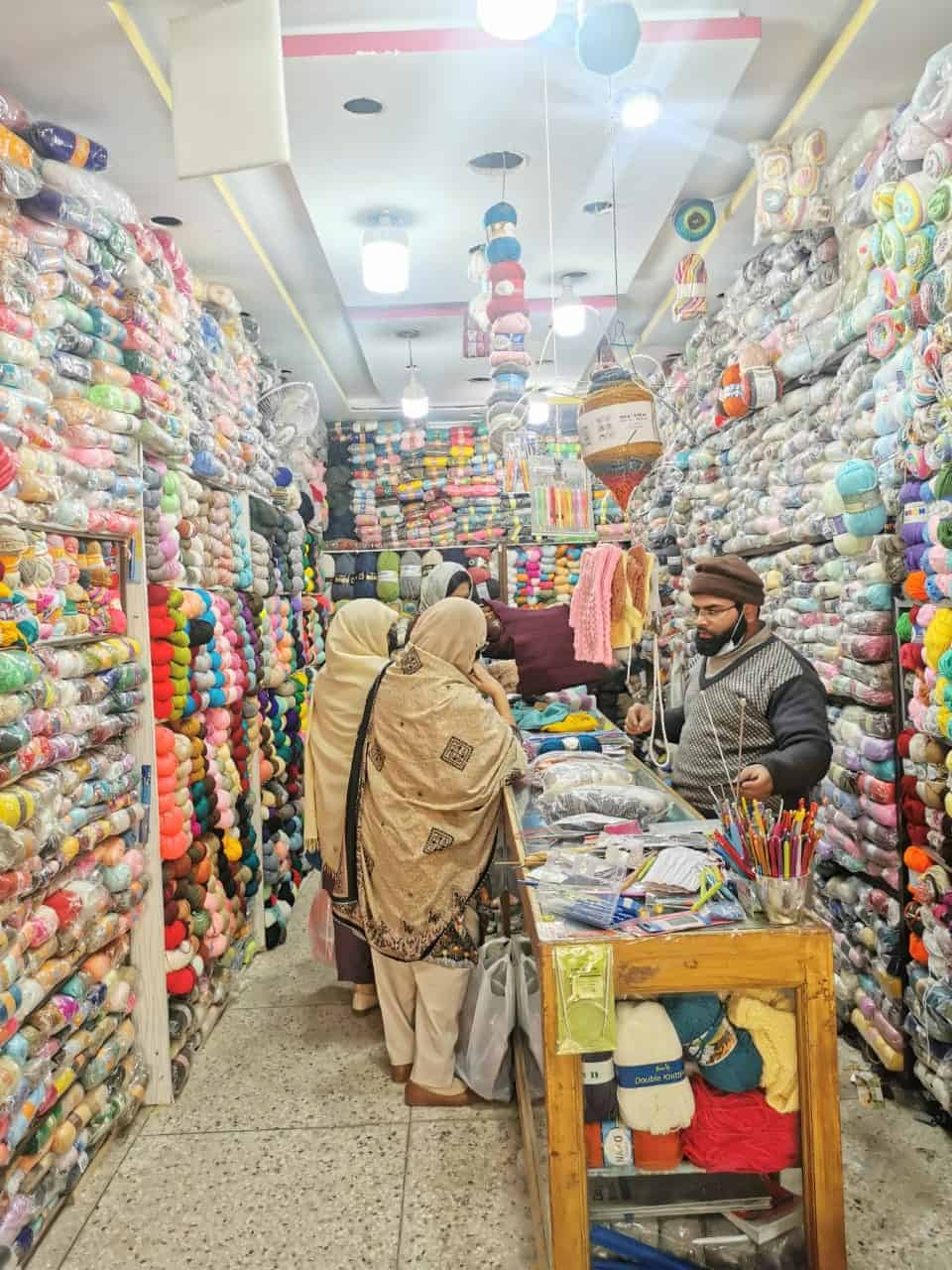A Pakistani man attends to customers in a yarn shop.