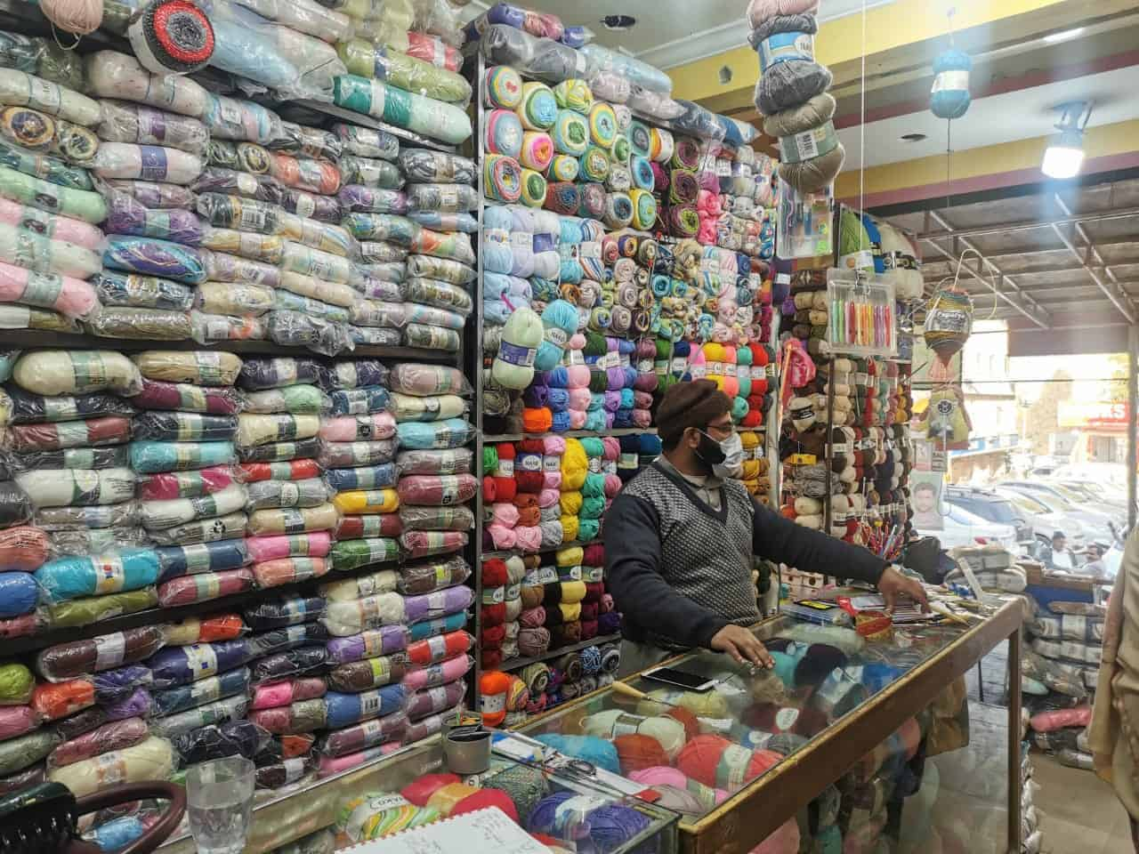 A Pakistani man wearing a face mask standing in a shop of colorful yarn.