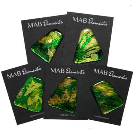 Three and four-sided stone-like pins with curved edges in yellow and green on black backings that read MAB Elements, HANDMADE IN OHIO.