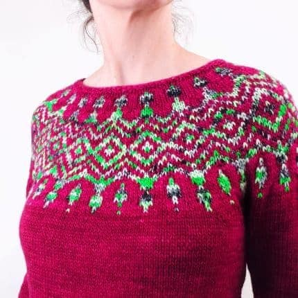 A fuchsia sweater with a bright green colorwork yoke.