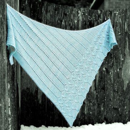 An aqua lacy triangle shawl.
