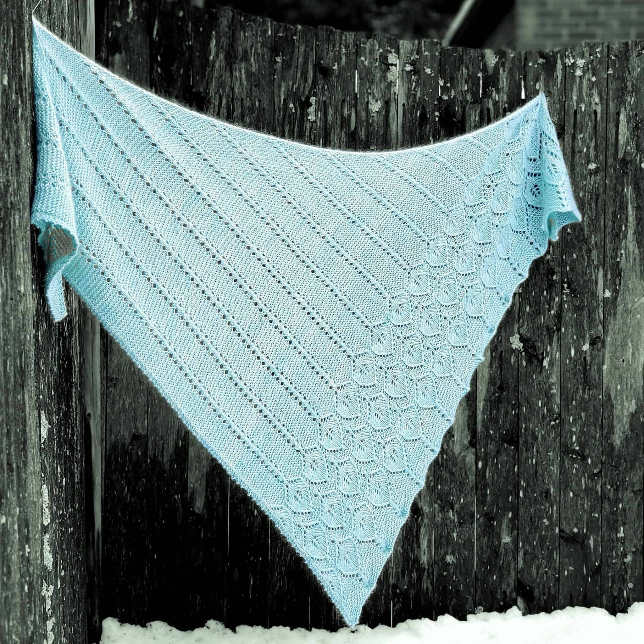 An aqua lacy triangle shawl.