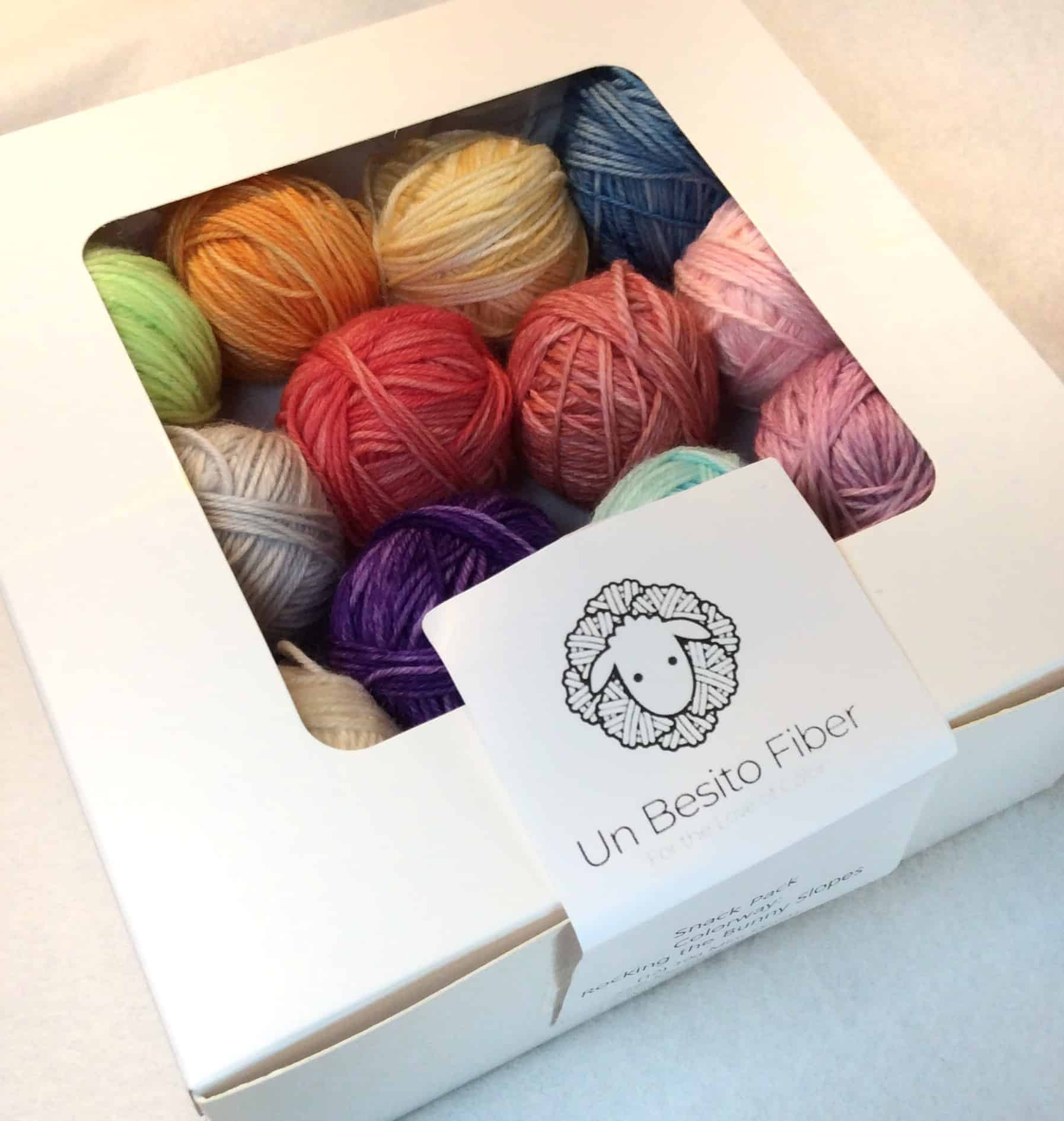 A cake box of brightly colored yarn balls.