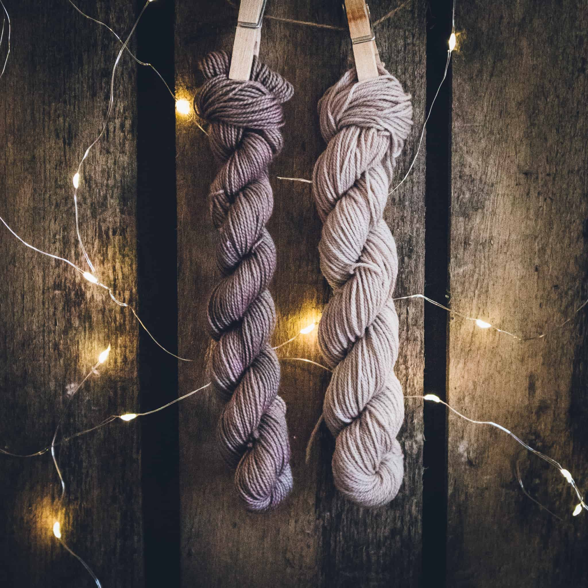 Skeins of gray yarn hanging on wooden clothespins.