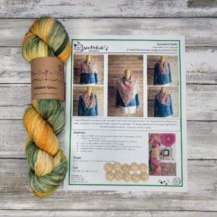 A skein of yellow and green yarn next to a printed knitting pattern.