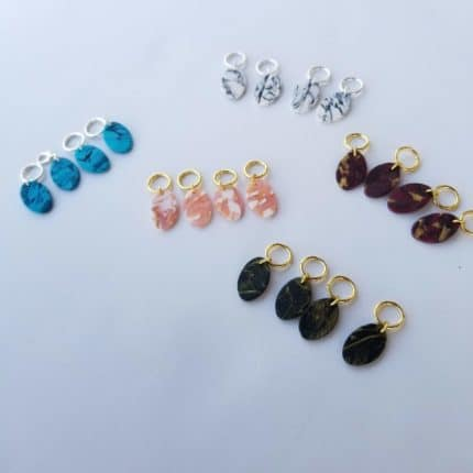 Blue, pink, gray, brown and black stone-like stitch markers.