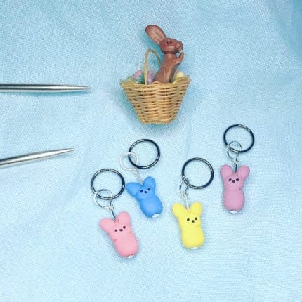 Pink, blue and yellow marshmallow Peeps charms, with a chocolate bunny in a basket.
