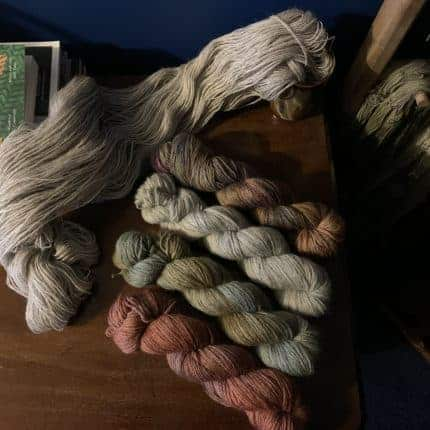 Skeins of organge, green, gray and brown yarn.