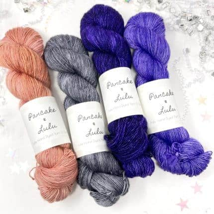 Skeins of pink, gray, blue and purple yarn.