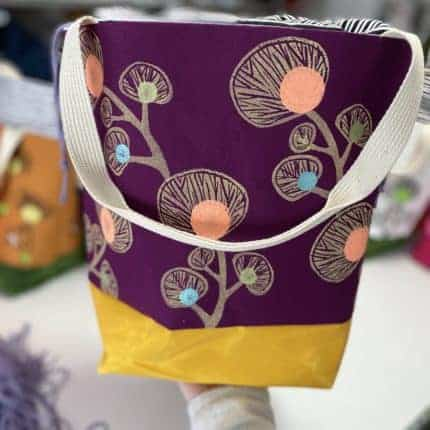 A purple, pink and yellow floral tote bag.