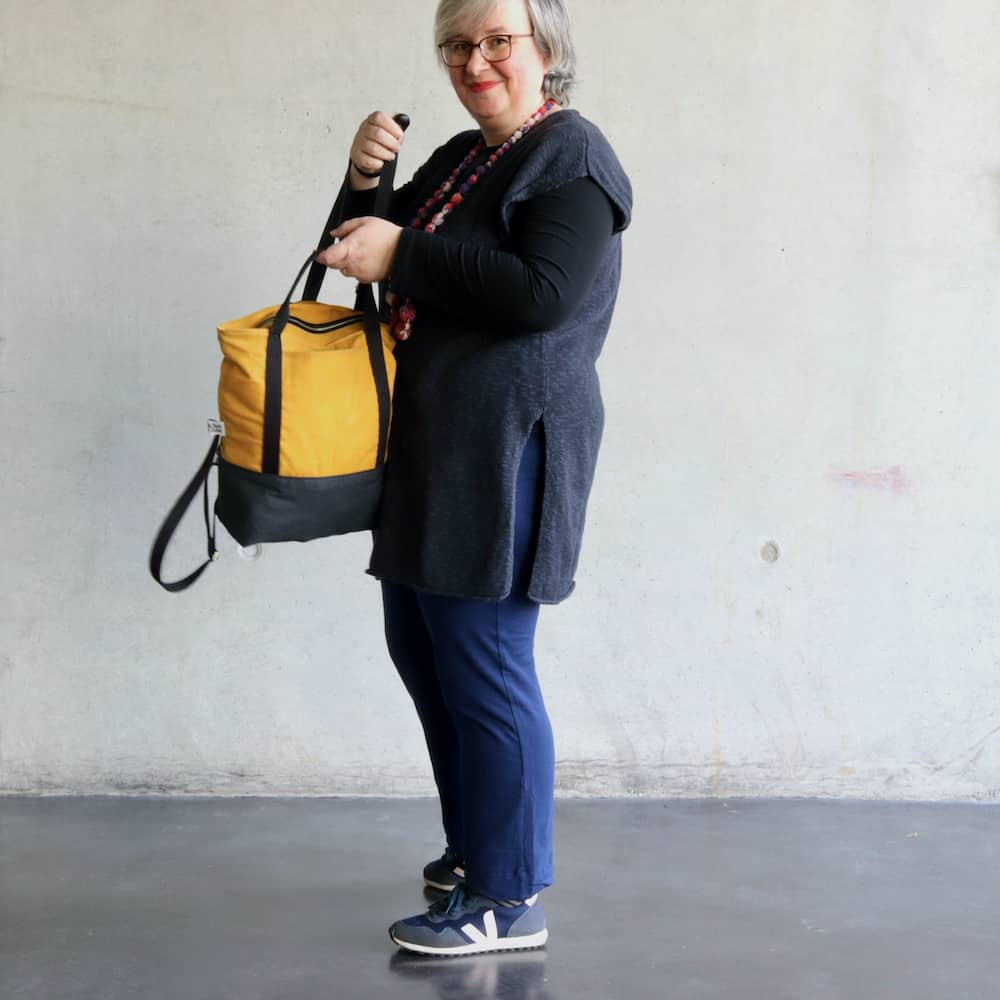 A woman holds a yellow backpack.