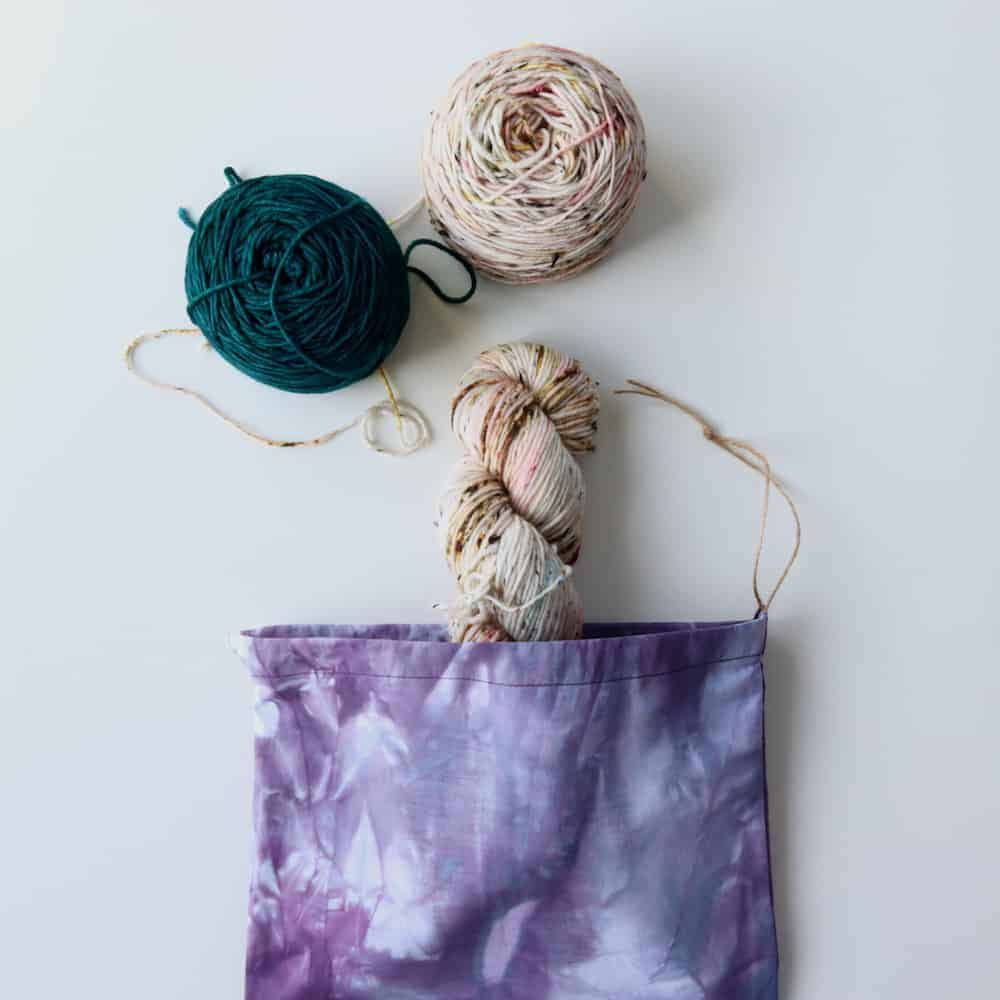 A purple dyed bag holding a skein of speckled pink yarn.