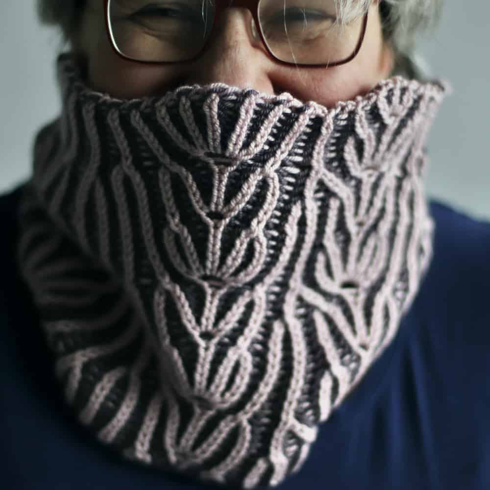 A woman in glasses wears purple brioche cowl.