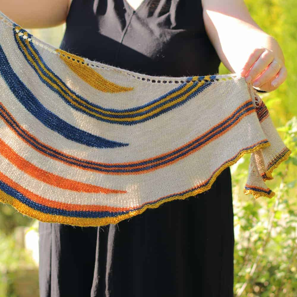 A yellow, blue, orange and cream striped crescent-shaped shawl.