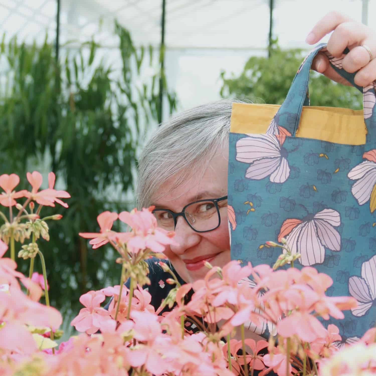 A woman with gray hair peeking out from behind a blue floral bag.
