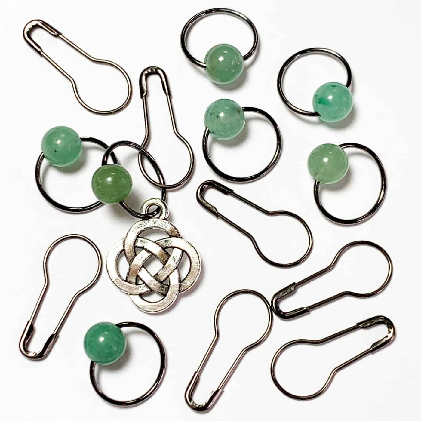 A silver Celtic knit and ring stitch markers with green beads.