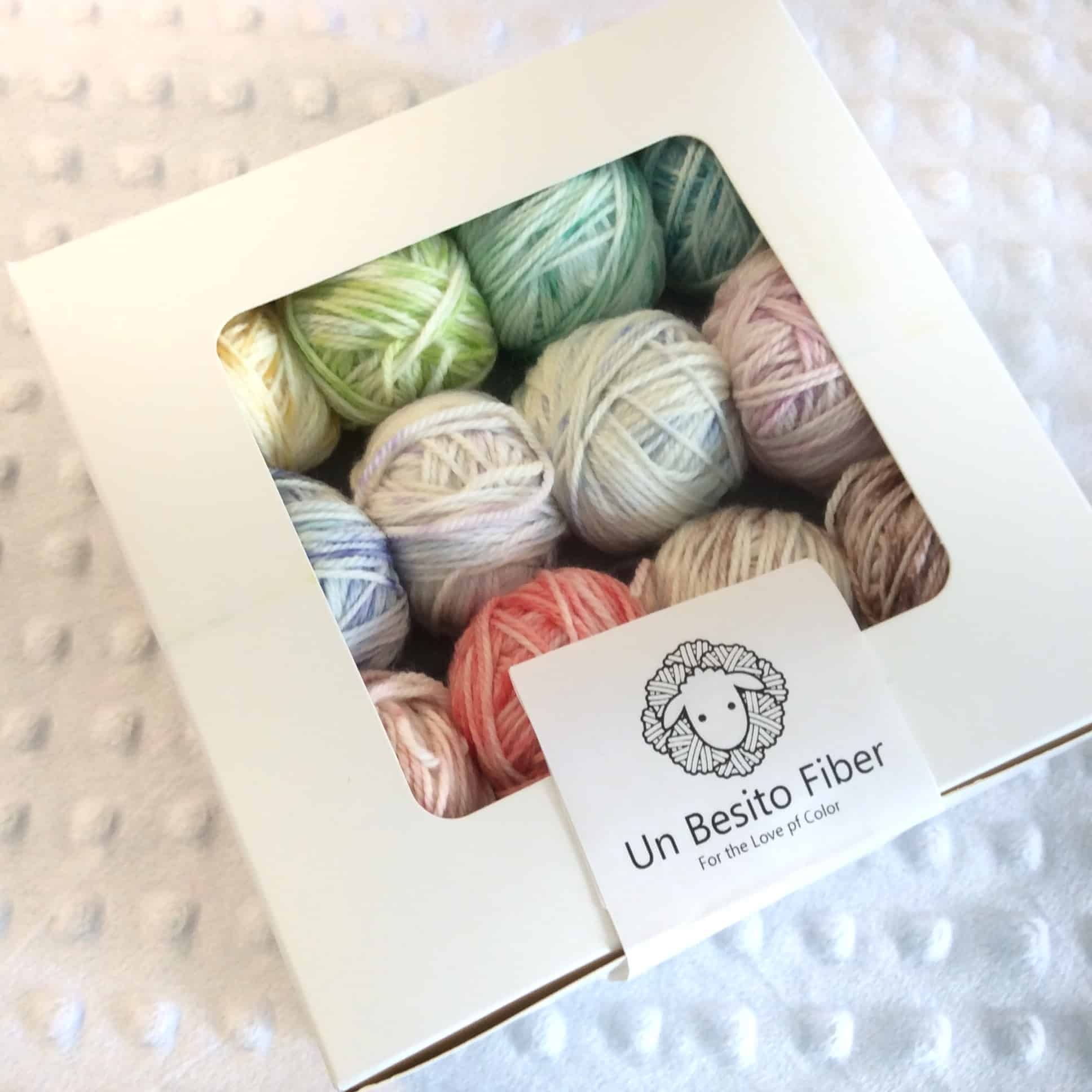 Balls of pastel yarn peer out of a clear-windowed bakery box.