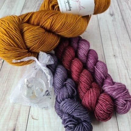 Purple, pink and gold skeins of yarn.