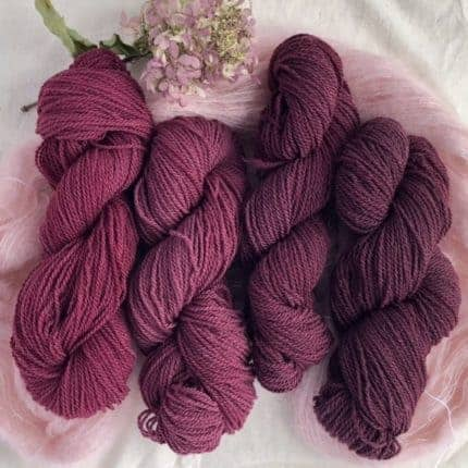 Four skeins of wine-colored yarn.