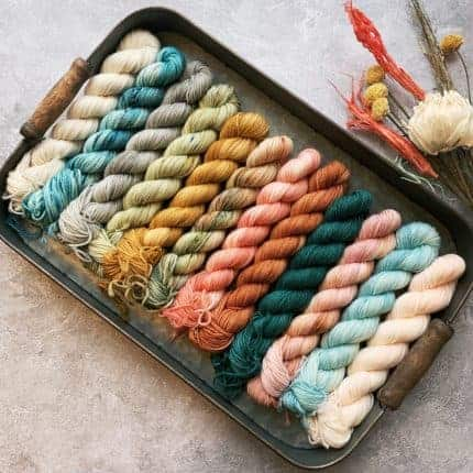 Mini skeins of turquoise, gold, pink, terracotta and blue yarn in a tray.