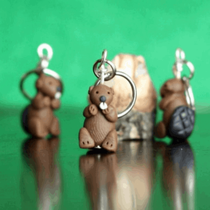 Beaver charms with silver ring attachments with a green background.