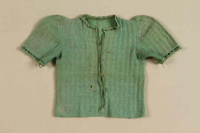 A worn child's green cardigan.