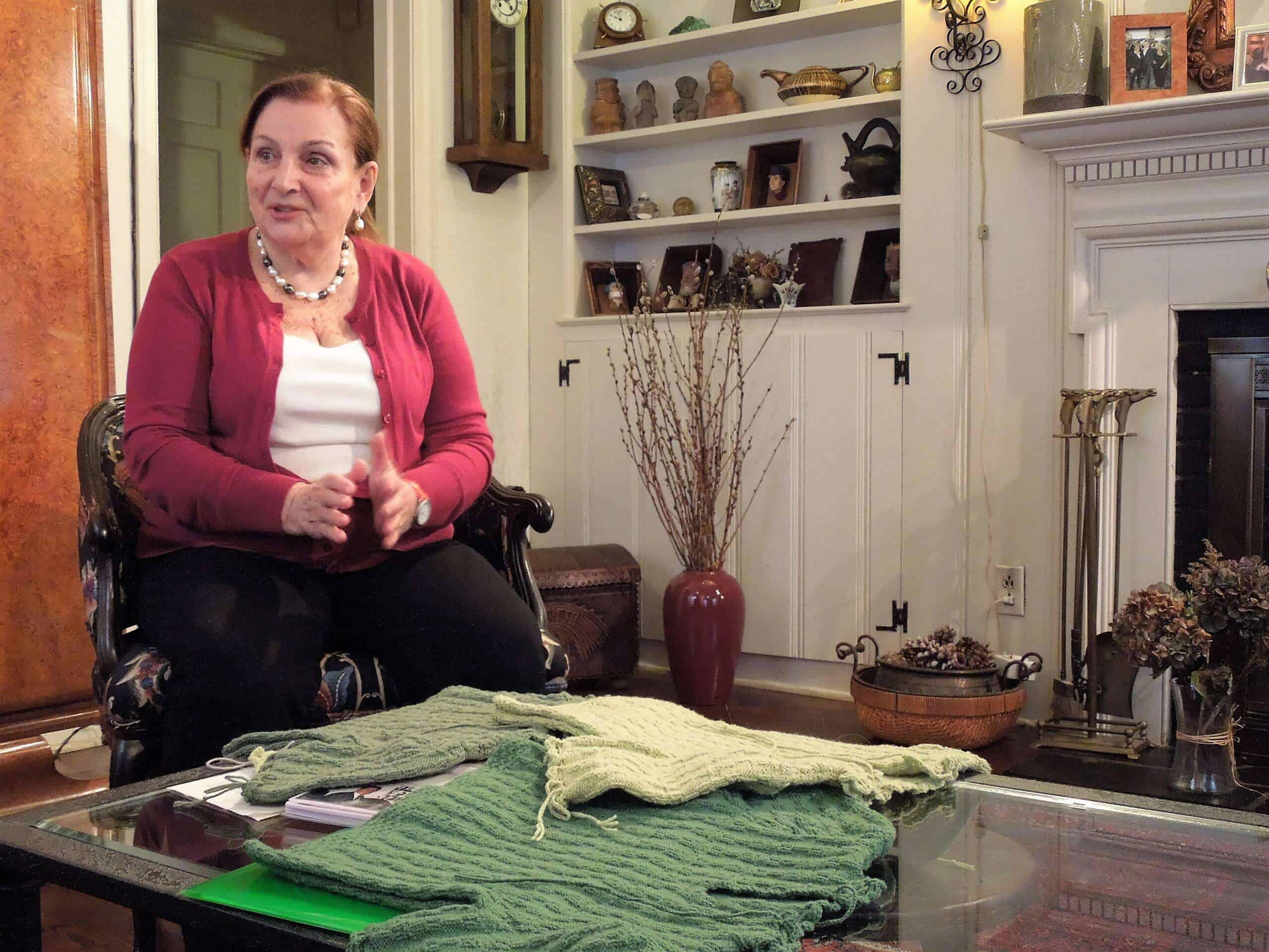 A woman sits next to a table filled with small green sweaters.