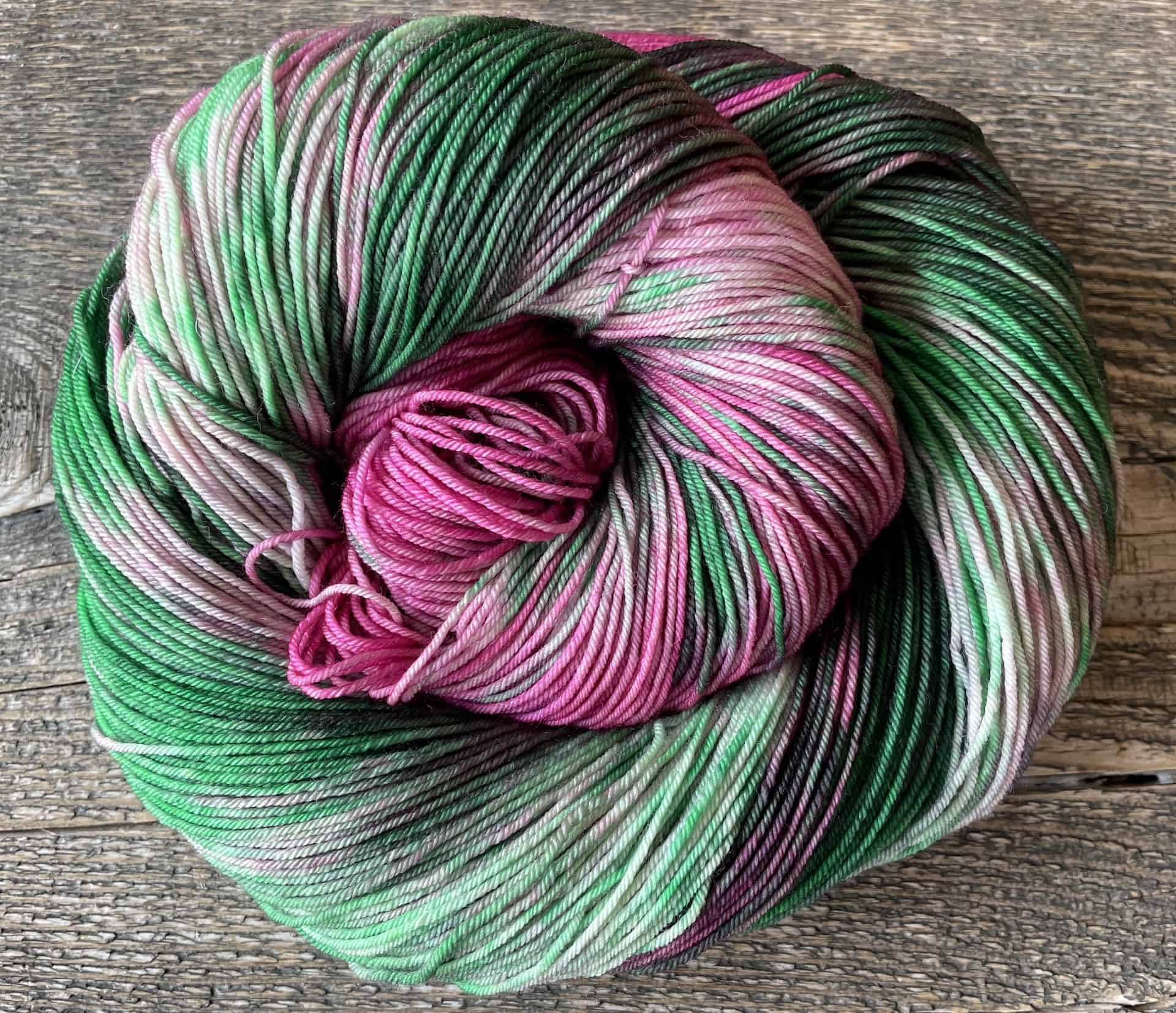 A spiral skein of green and pink yarn.