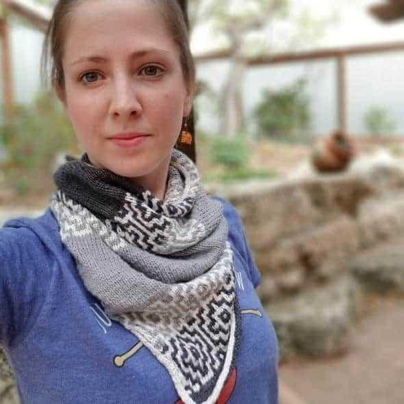 A woman wears a gray and white mosaic bandana.