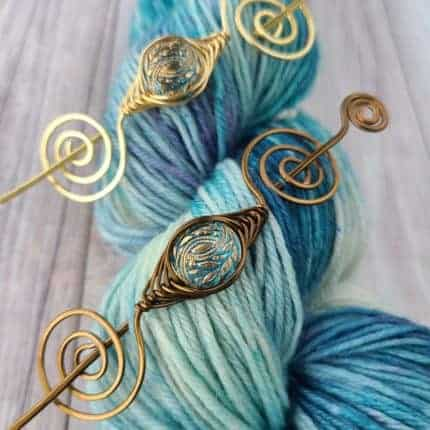 Gold swirled metal shawl pins atop a skein of light blue yarn.