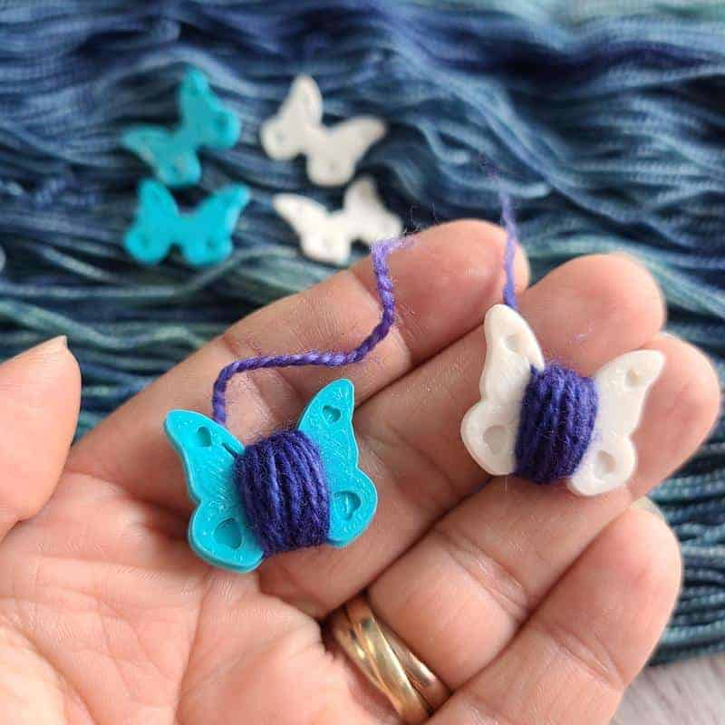 A hand holds blue and white plastic butterflies wrapped in purple yarn.
