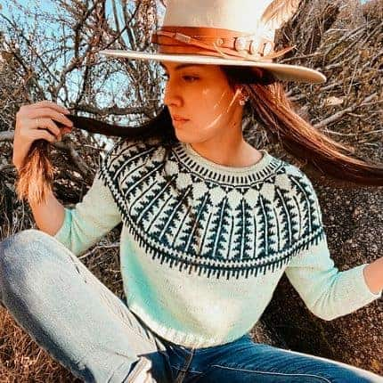 A long-haired woman in a wide-brim hat models a black and white colorwork sweater.