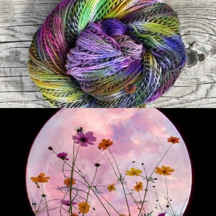 A skein of rainbow yarn above a photo of wildflowers in front of the moon.