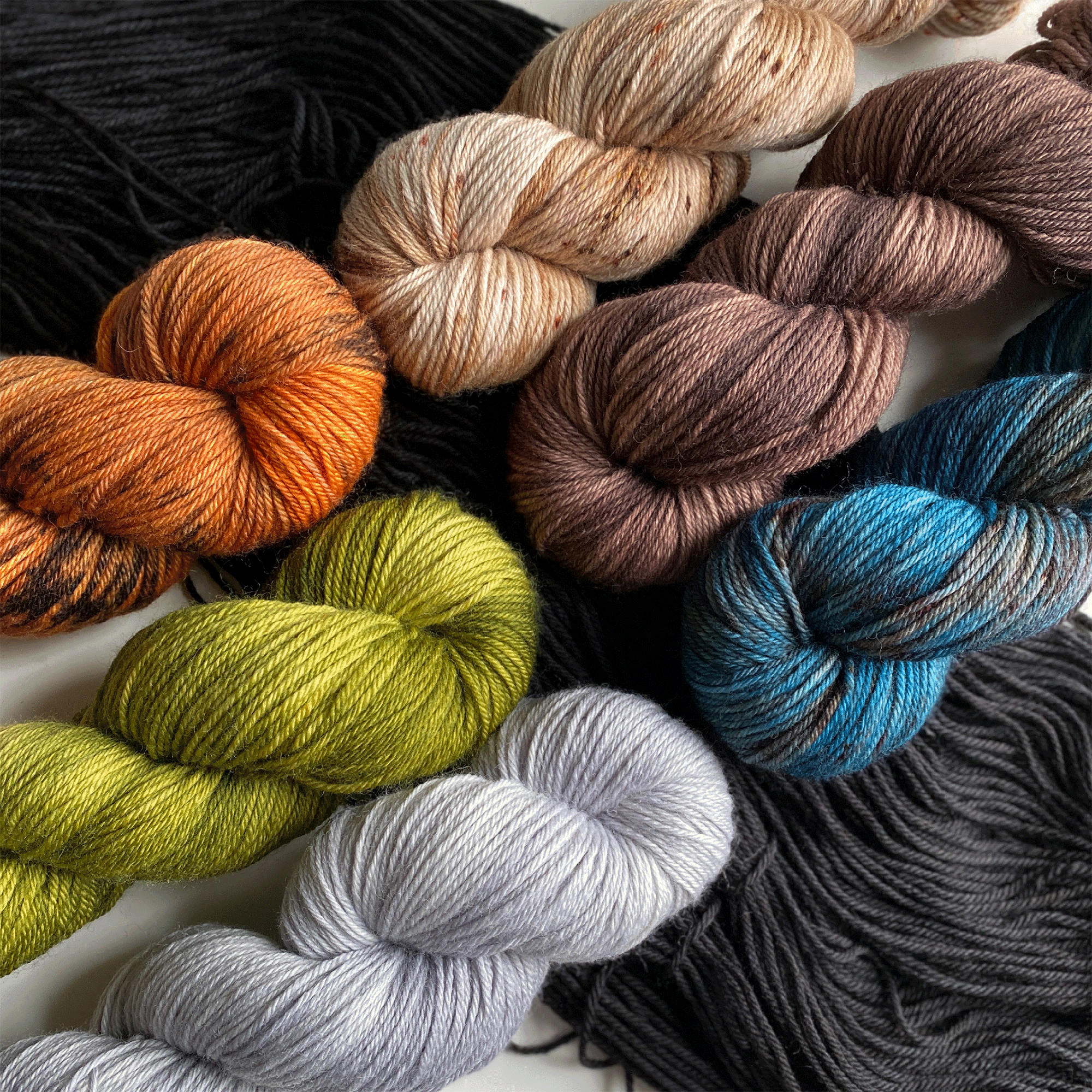 Skeins of orange, green, gray, peach, brown and blue and gray yarn.
