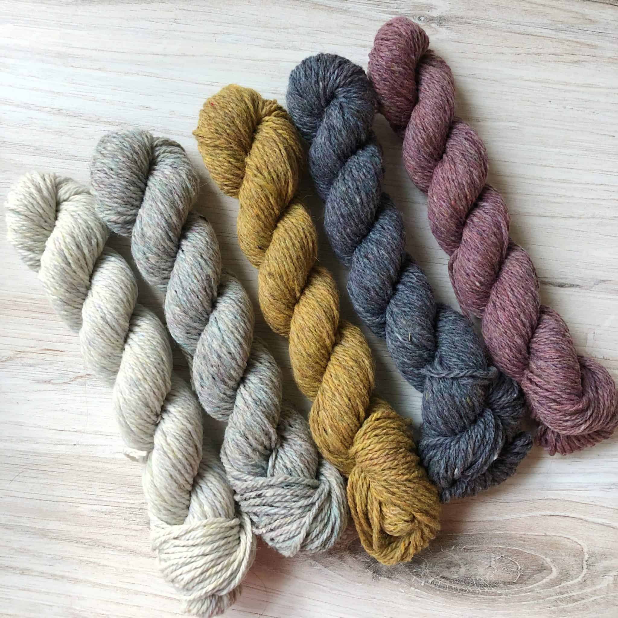 A set of white, gray, gold and pink skeins of yarn.