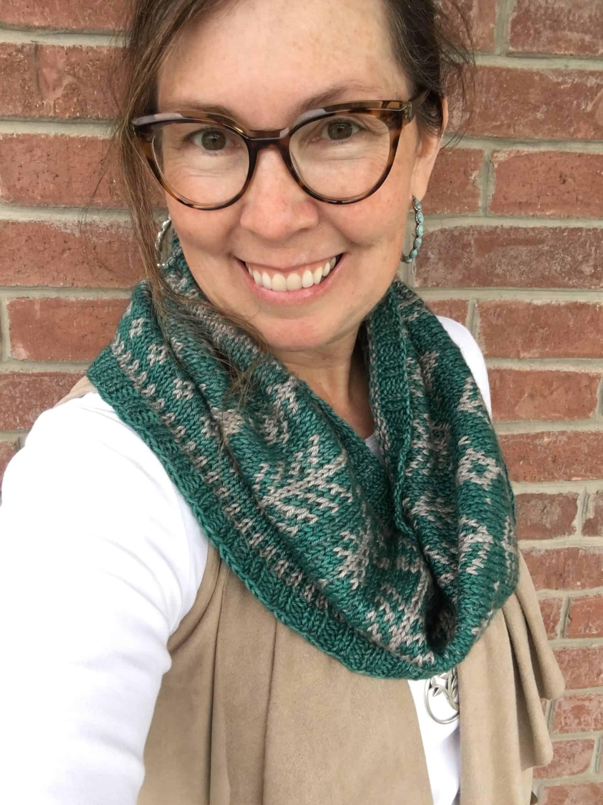 A woman wearing a green knit cowl.