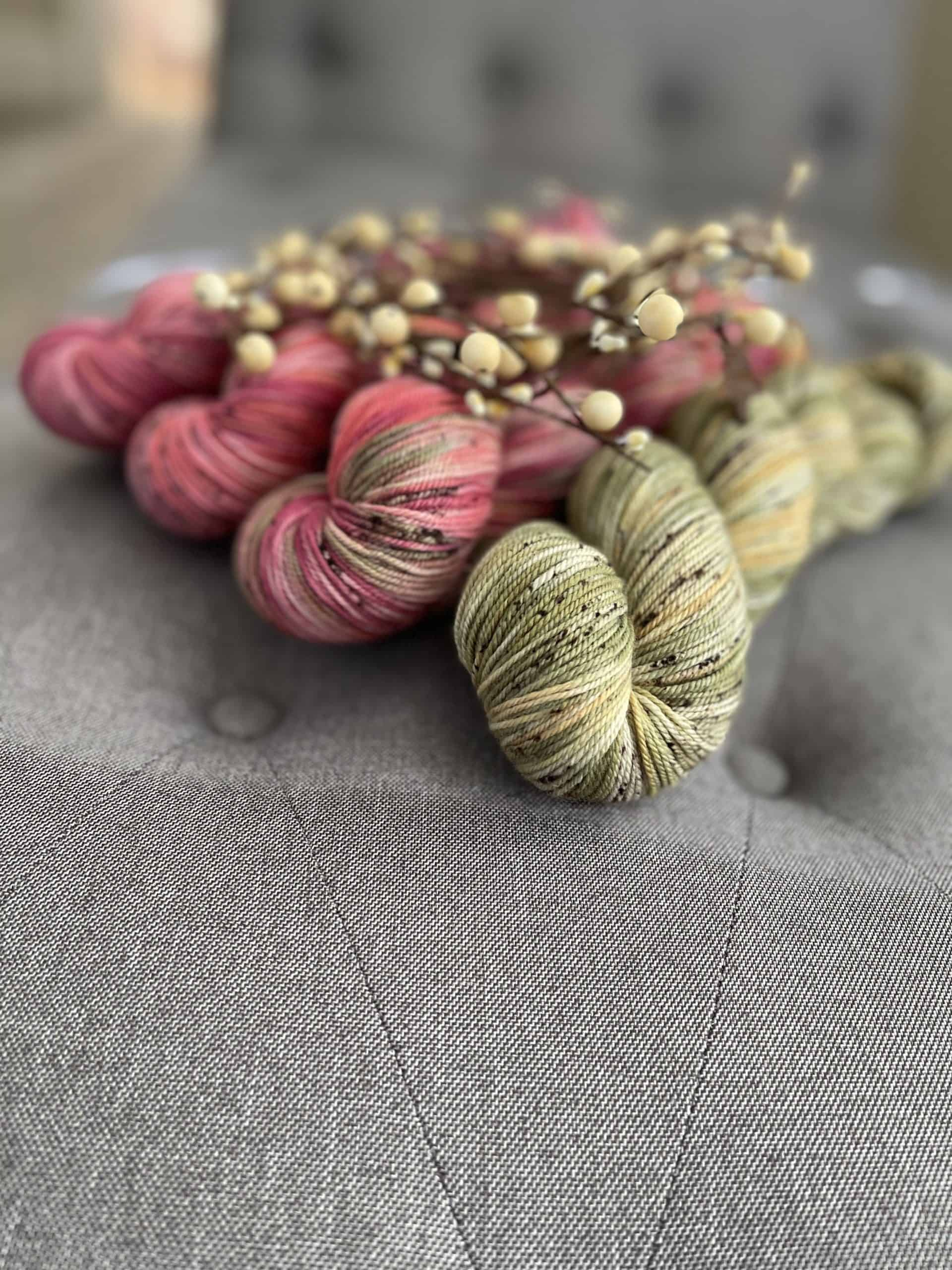 Pink and green yarn with branches on top.