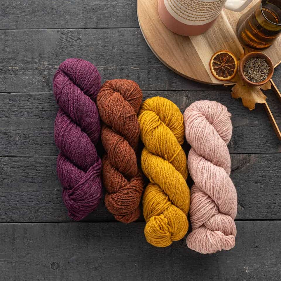 Purple, orange, gold and pale pink yarn.