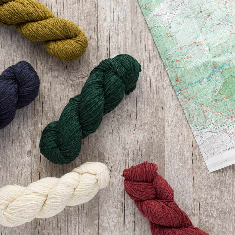 Gold, navy, forest green, white and red yarn next to a map.