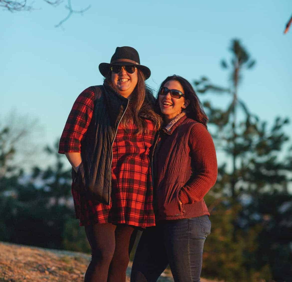 Two women wearing red posing together in wilderness.