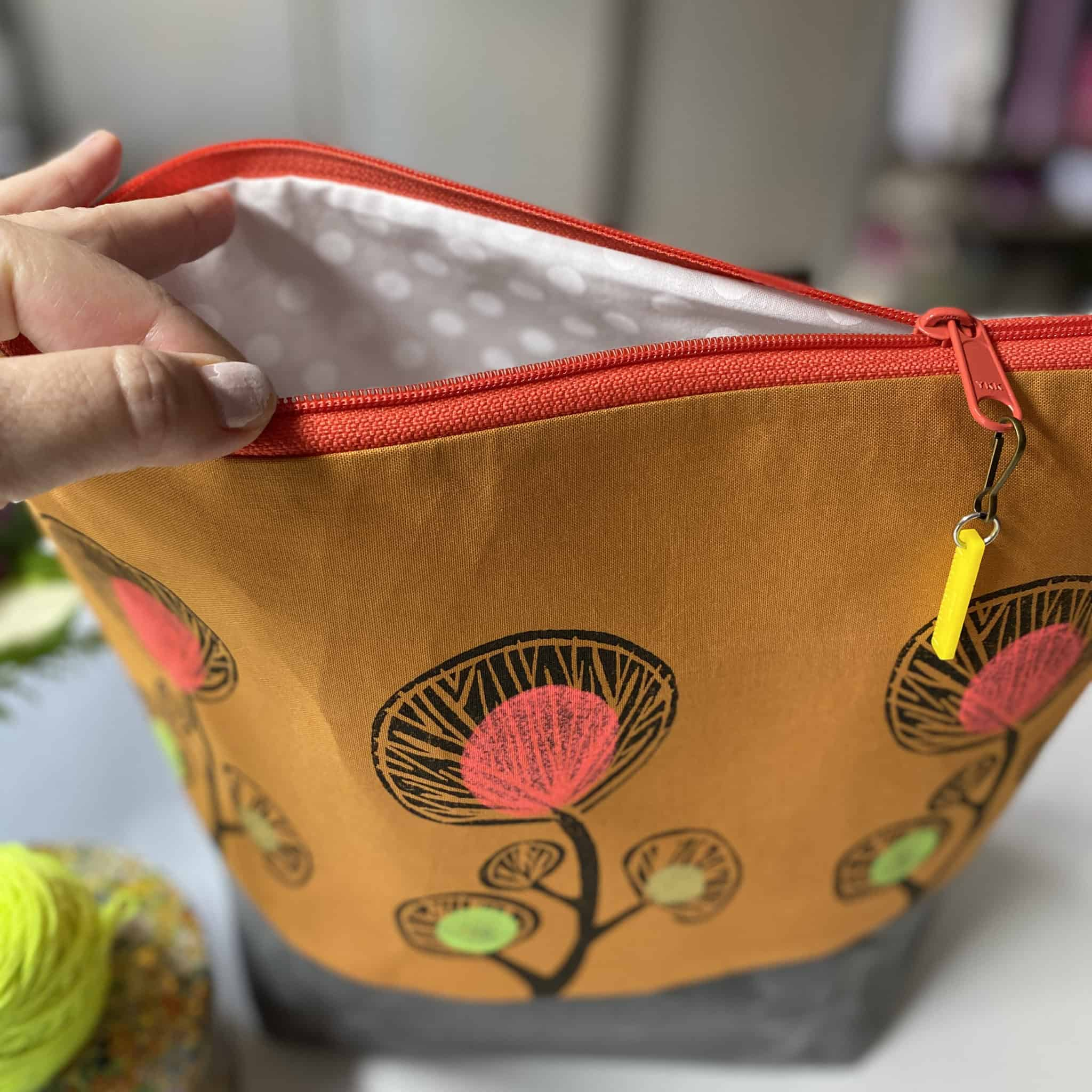 A gold zippered bag with flowers.