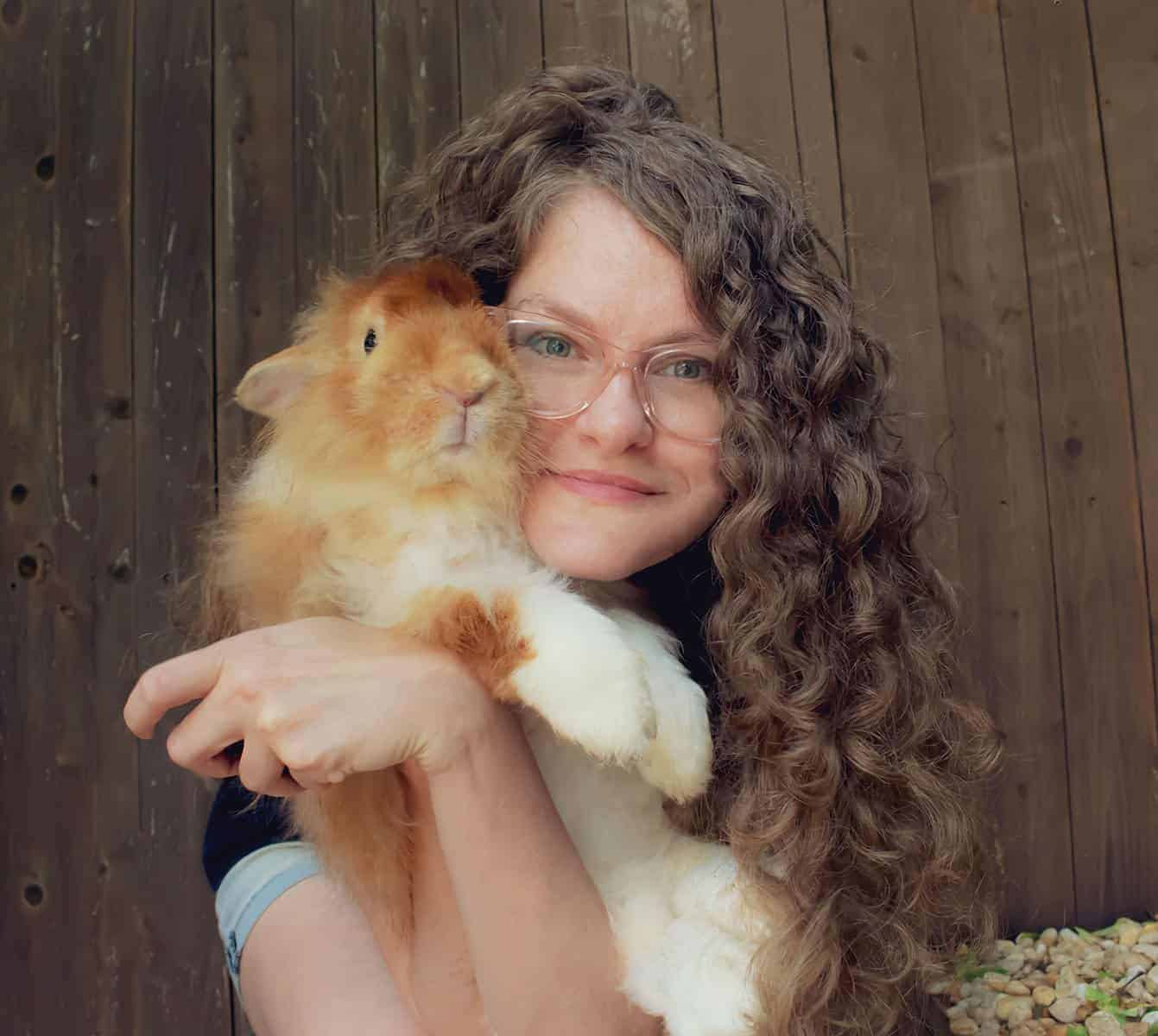 A woman with long curly hair holding a white and gold rabbit.