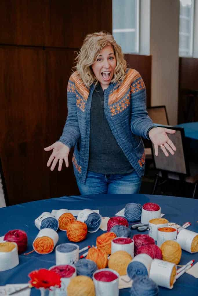 A woman wearing a blue and orange sweater stands over a table of colorful yarn.