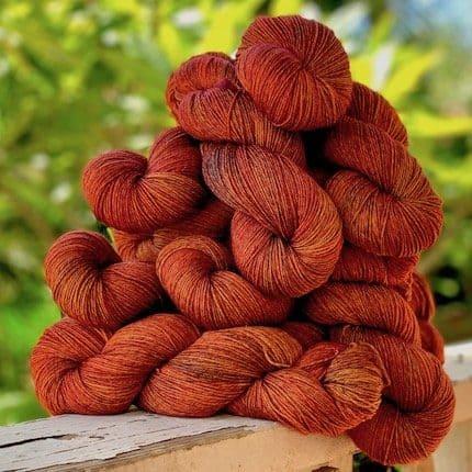 A pile of skeins of orange yarn.