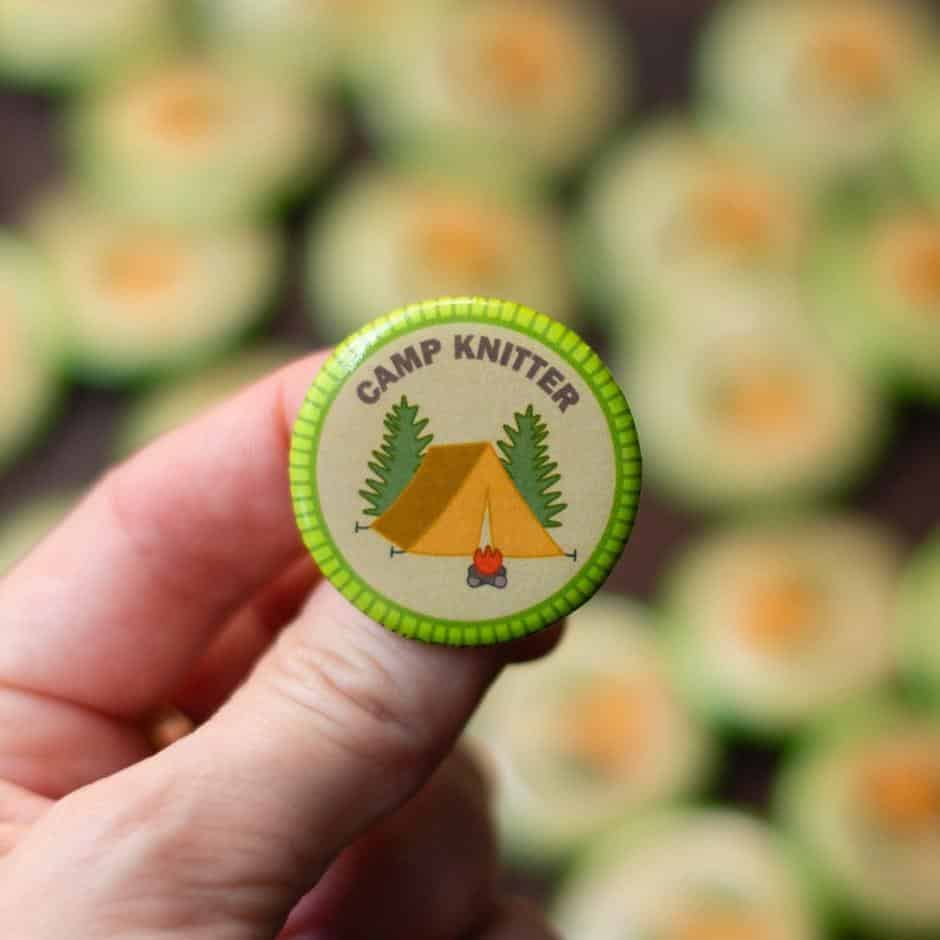 A green badge with a yellow tent between two pine trees that reads Camp Knitter.