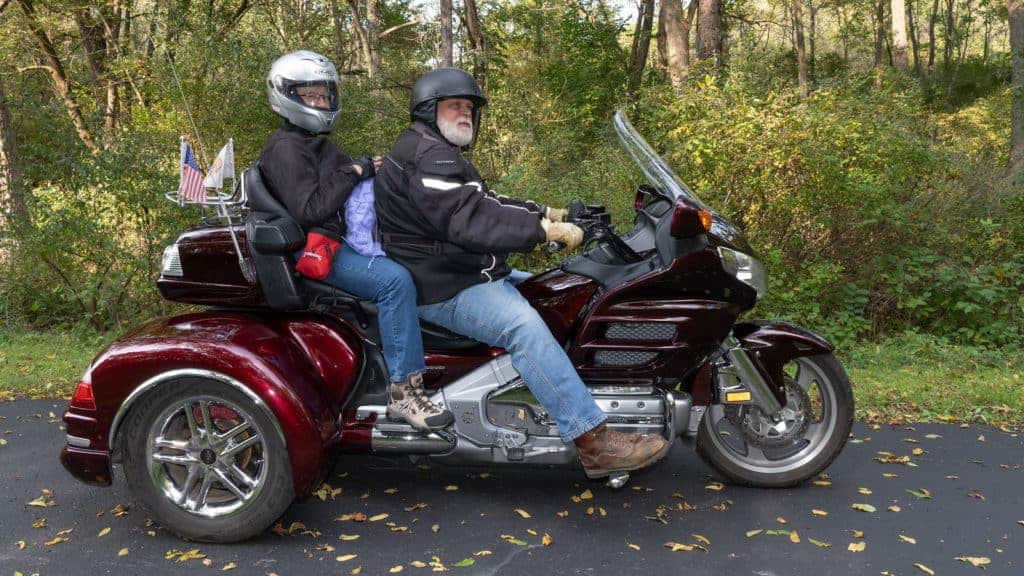 Two people on a motorcycle, the one in the back knitting on a purple project.