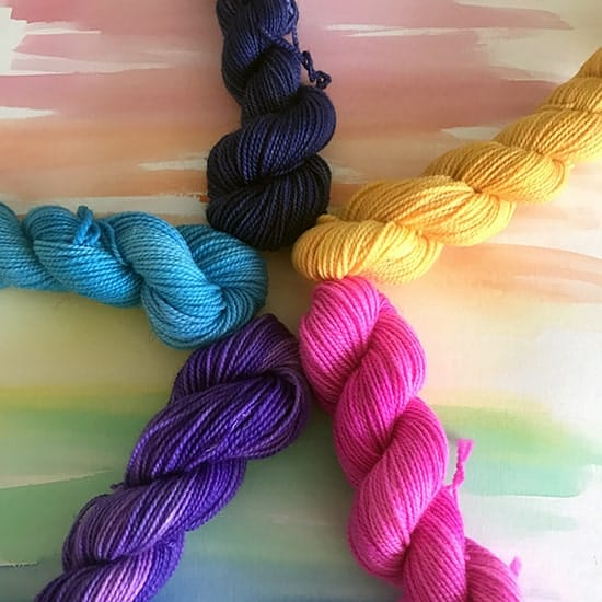 Pink, purple, blue, black and yellow mini skeins in a circle.